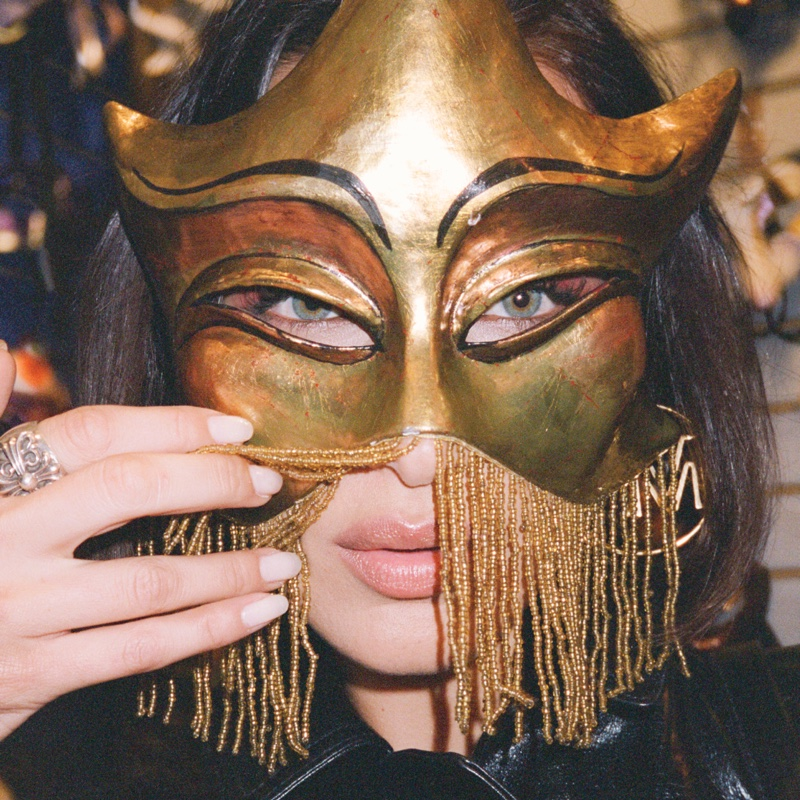 Wearing a mask, Bella Hadid poses in MICHAEL Michael Kors Travel Diaries.