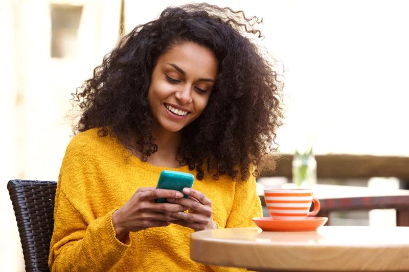 Black Woman Curly Hair Looking Phone