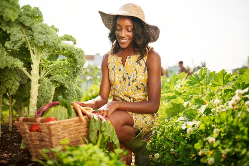 Black Woman Smiling Gardening Outdoors Hat Yellow Dress