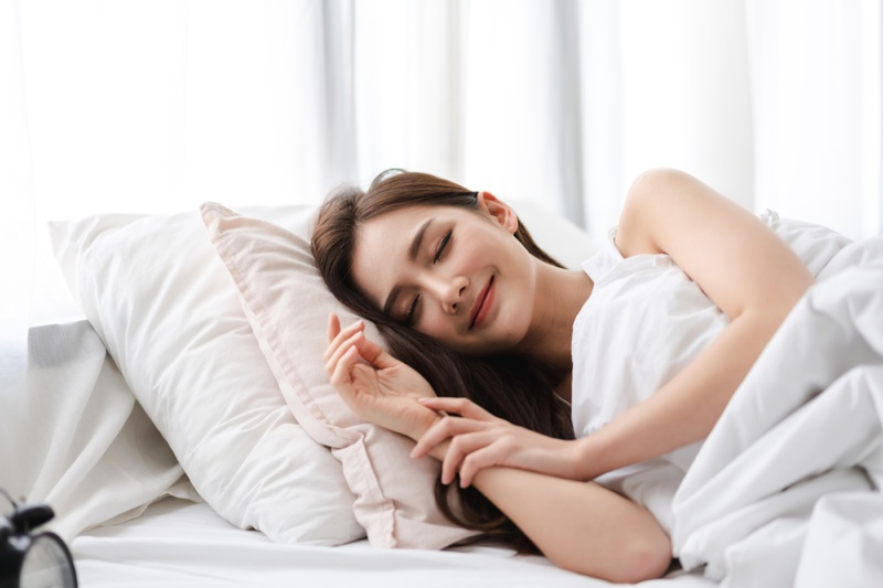 Smiling Asian Woman Sleeping Pillows