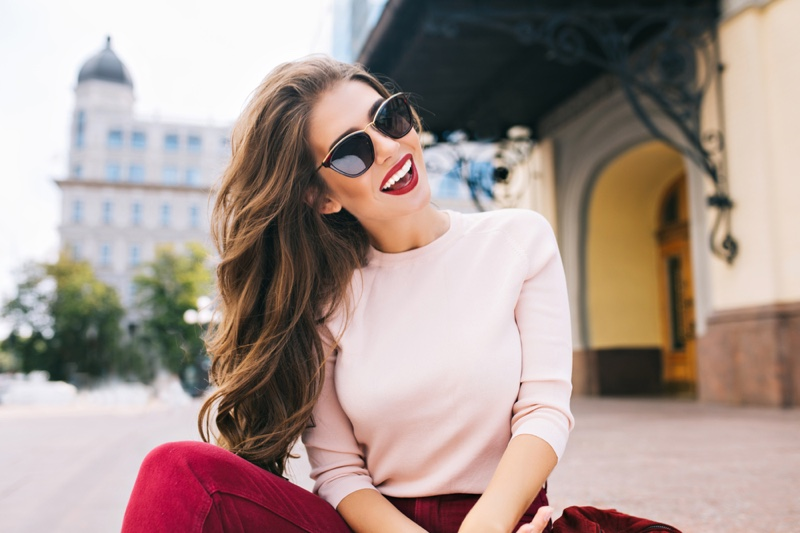 Smiling Model Pink Sweater Red Pants Sunglasses
