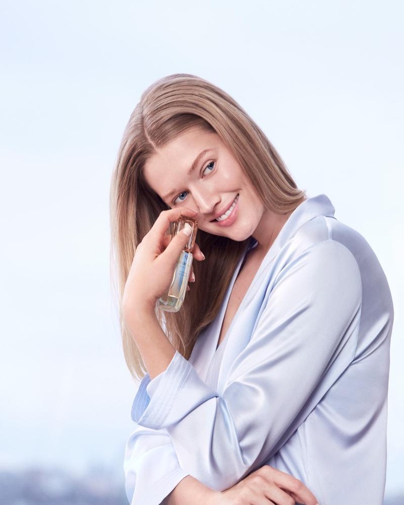 Model Toni Garrn poses with Clé de Peau Beauté Le Serum bottle.