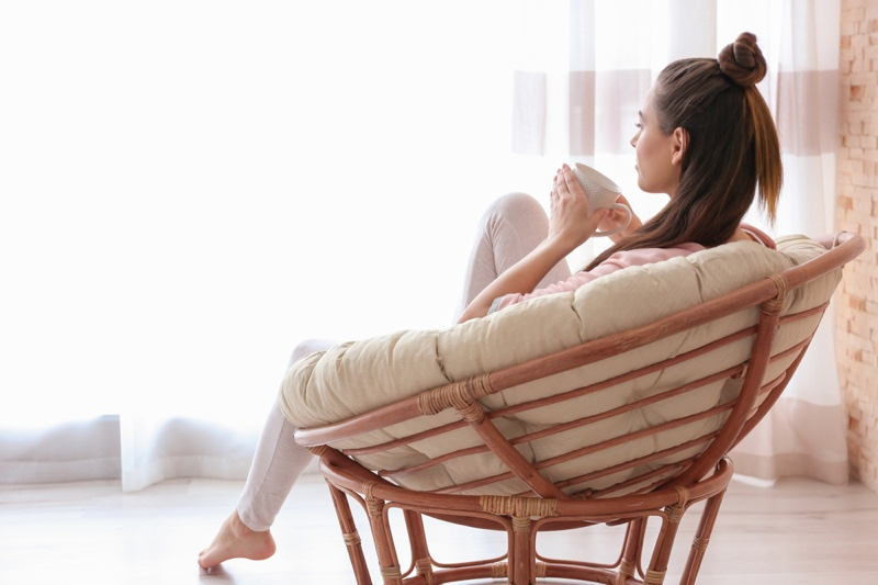 Woman Back Relaxing Chair Near Window Curtains