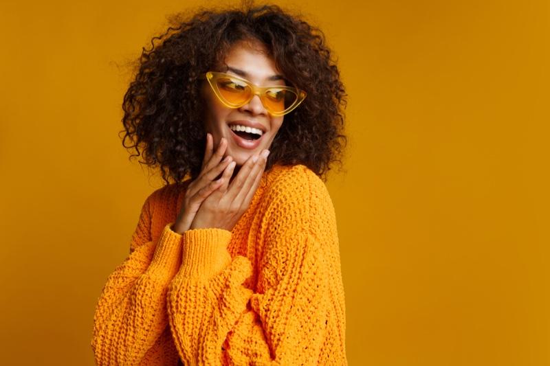 Smiling Black Woman Curly Hair Yellow Sweater Cat-Eye Sunglasses