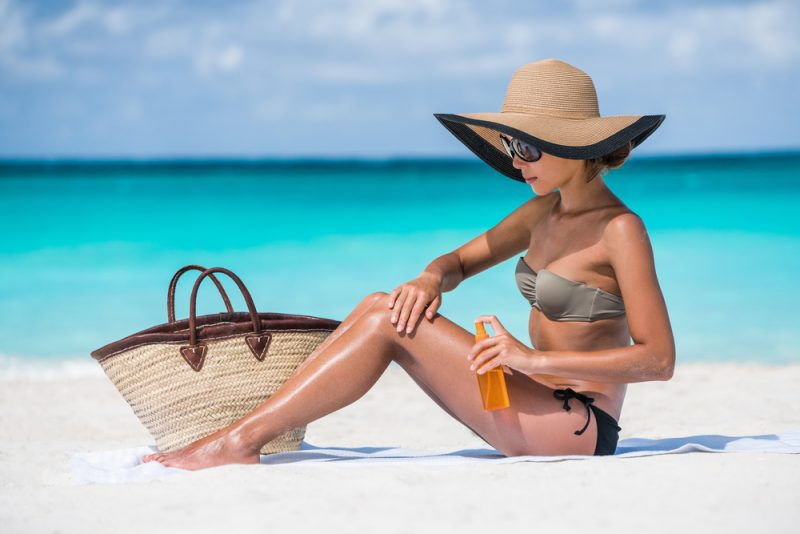 Woman in Hat at Beach Getting Tan