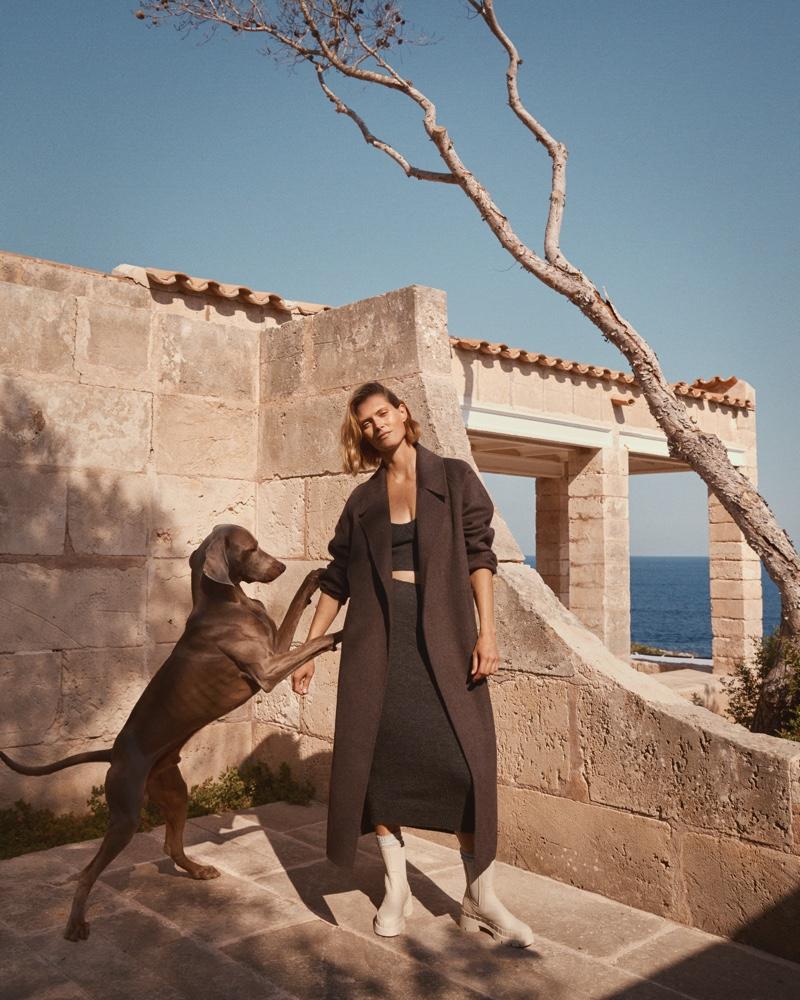 Posing with a dog, Malgosia Bela models Mango fall 2020 collection.