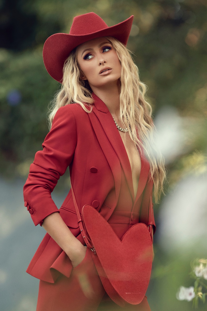 Suiting up in red, Paris Hilton wears DSquared2 jumpsuit and blazer.