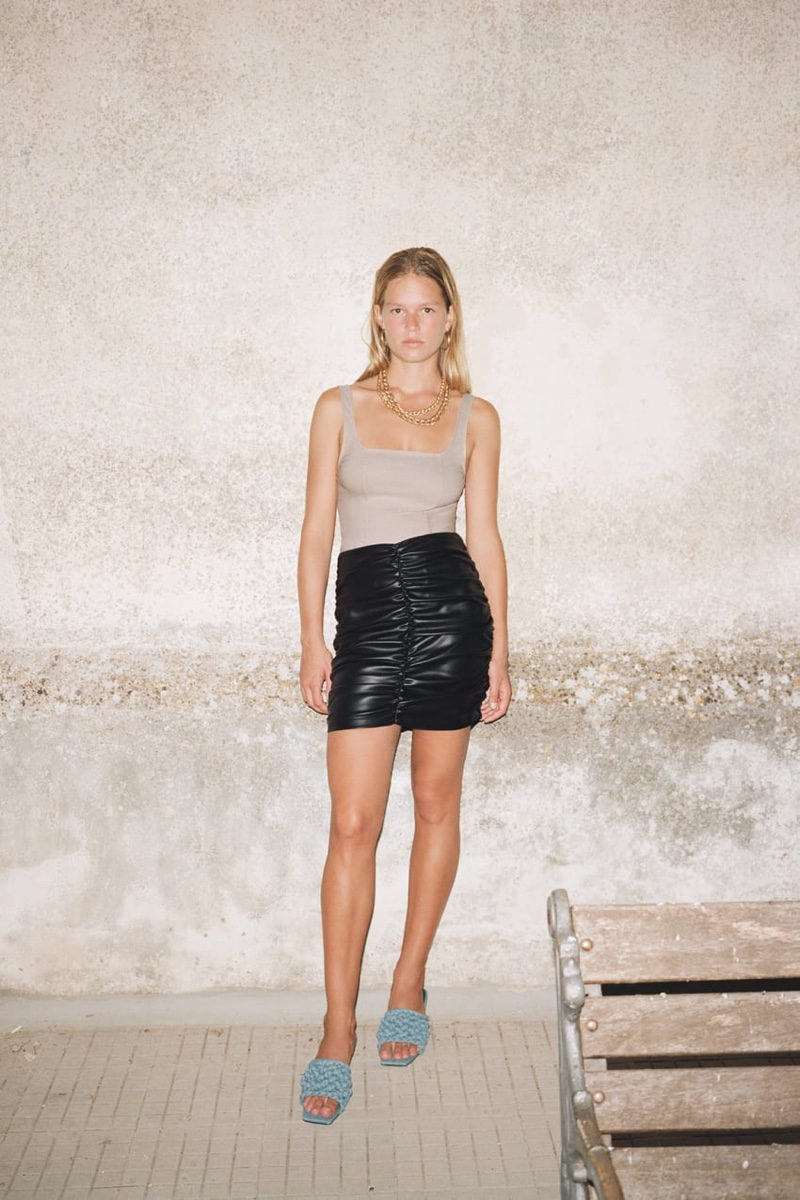 Anna Ewers wears Zara tank top and draped faux leather skirt.
