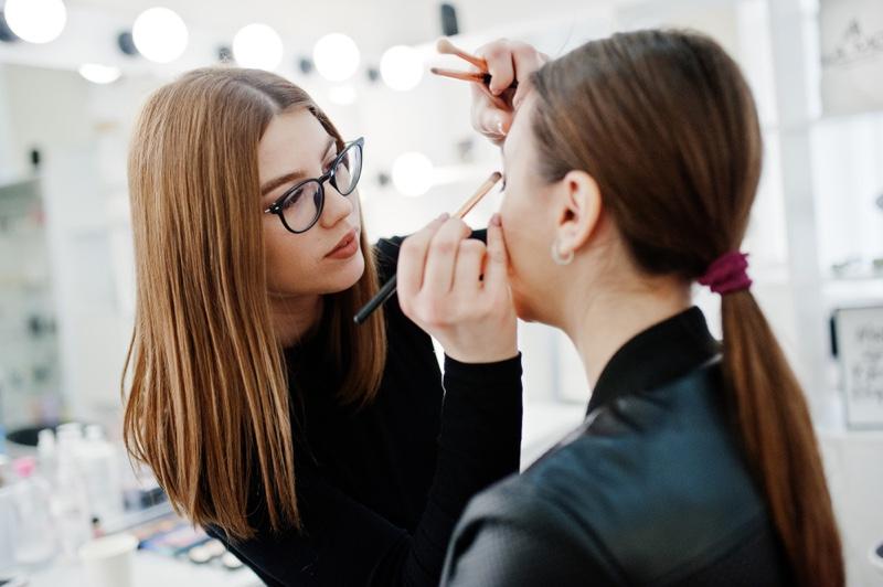 Attractive Makeup Artist Wearing Glasses Applying Makeup on Model