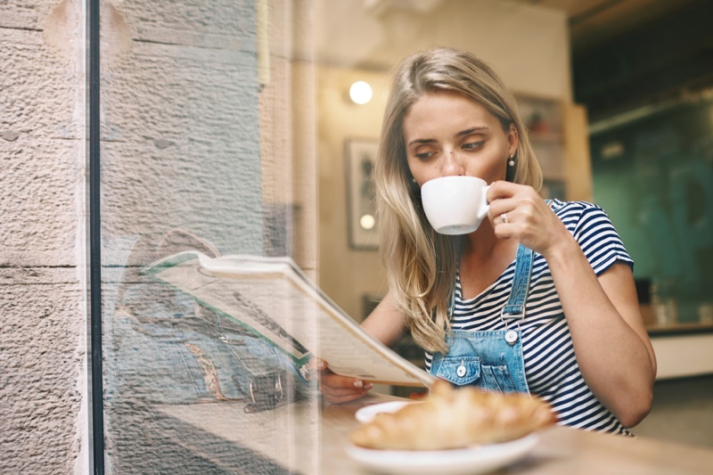 Blonde Woman Reading Magazine Drinking Coffee Cafe
