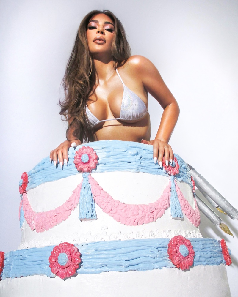 Rocking a bikini top in a tiered cake, Kim Kardashian poses for KKW Beauty Opalescent campaign.