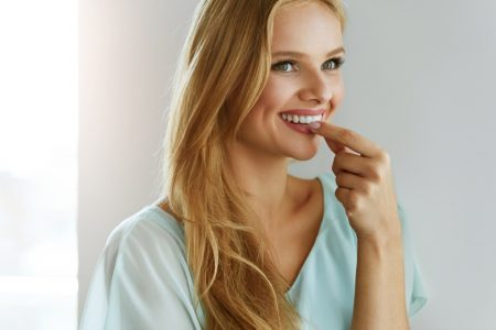 Smiling Blonde Model Taking Pill Vitamin Supplement
