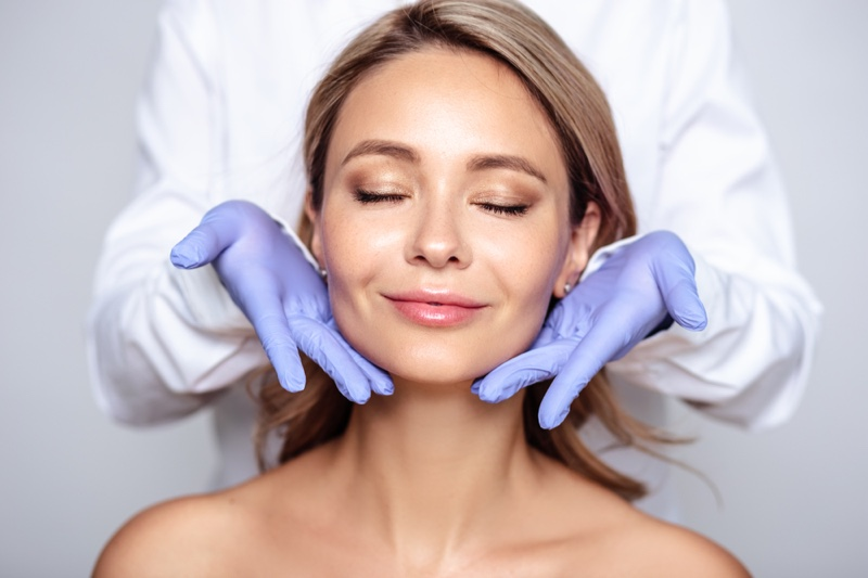 Smiling Woman Doctor's Hand Spa Surgery Face Concept