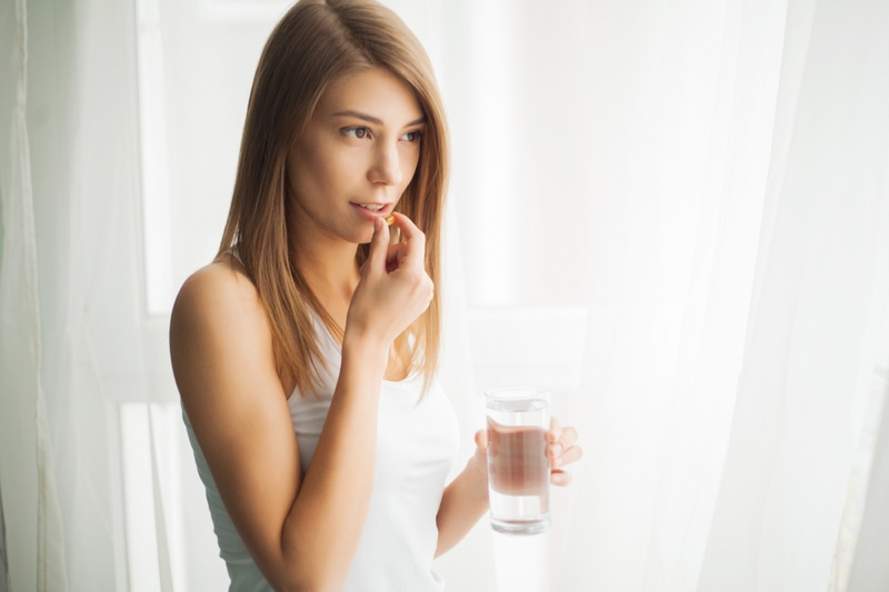 Woman Taking Pill Vitamin Supplement Holding Water Glass