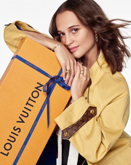 Alicia Vikander poses with an oversized Louis Vuitton gift box for the brand's holiday 2020 campaign. The actress charms in a yellow Louis Vuitton coat, complete with leather monogram detailing.