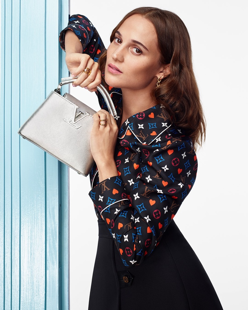 Taking hold of a silver handbag, Alicia Vikander stars in Louis Vuitton's holiday 2020 campaign. The famous friend of the brand dons a multicolor monogram blouse with a dark skirt.
