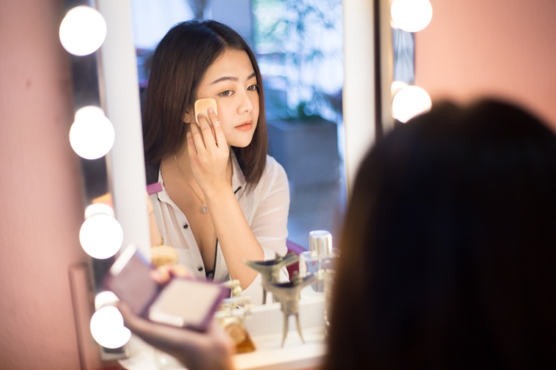 Asian Girl Applying Makeup Lighted Vanity Mirror