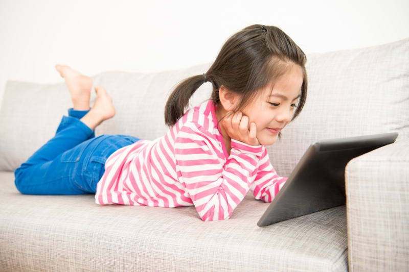 Asian Girl Viewing Tablet Couch