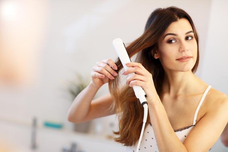 Brunette Model Straightening Long Hair Flat Iron
