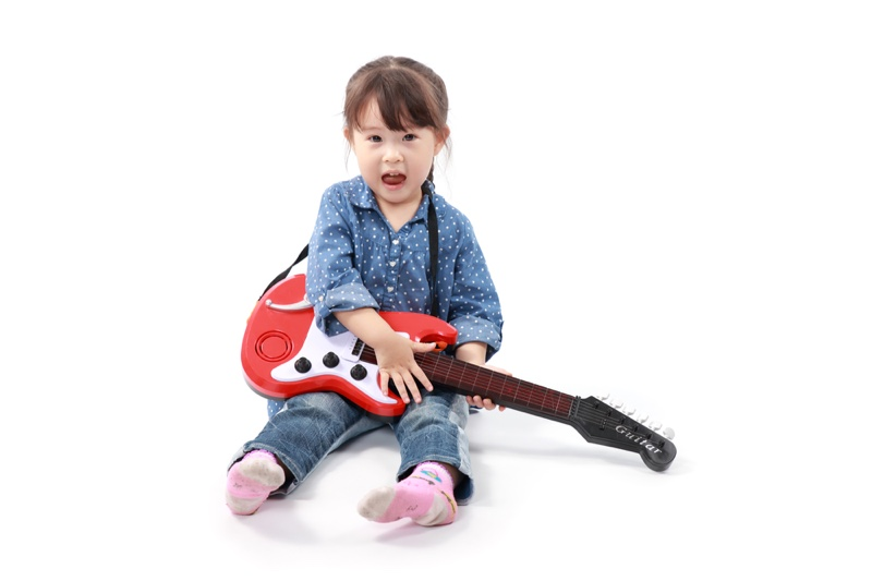 Little Asian Girl Playing Toy Guitar