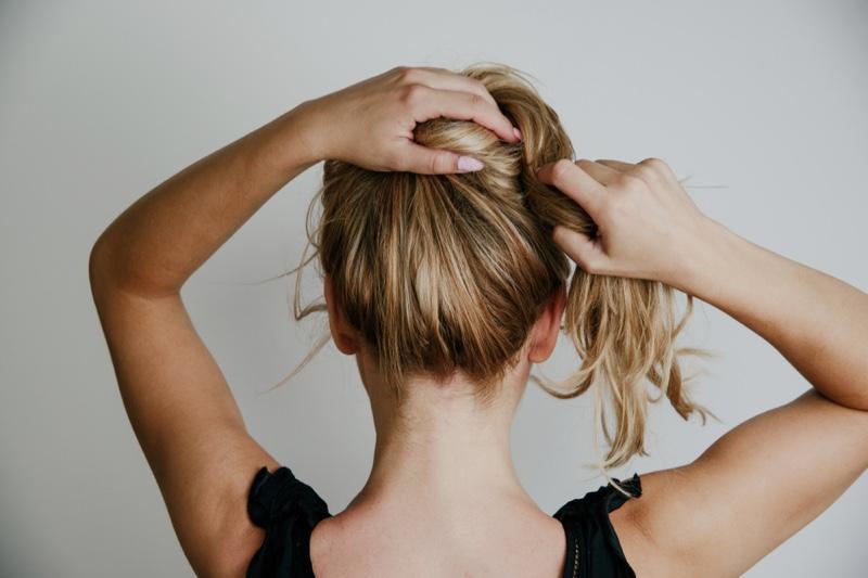 Woman Tying Up Blonde Hair
