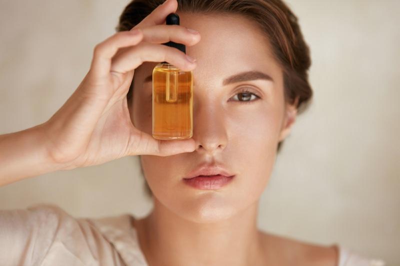 Beauty Model Oil Bottle Holding Closeup Face