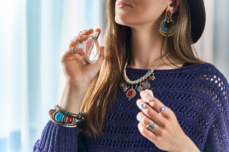 Bohemian Woman Holding Fragrance Bottle Layered Jewelry