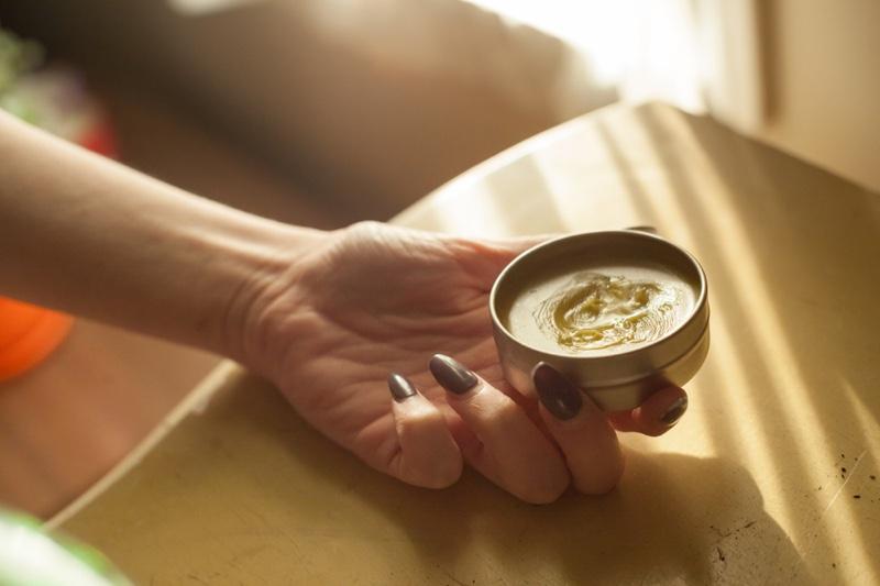 Long Nails Woman's Hand Holding CBD Balm Cream