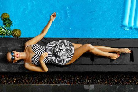 Model Striped One-Piece Swimsuit Hat Poolside Fashion