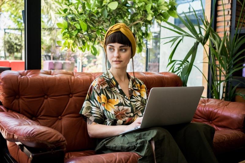 Stylish Woman Sitting Leather Sofa Hawaiian Shirt Laptop