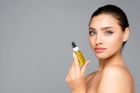 Beauty Model Holding Oil Bottle