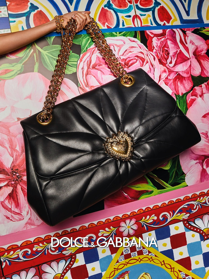 Dolce & Gabbana features a gold heart embellishment on a handbag in its spring-summer 2021 campaign.