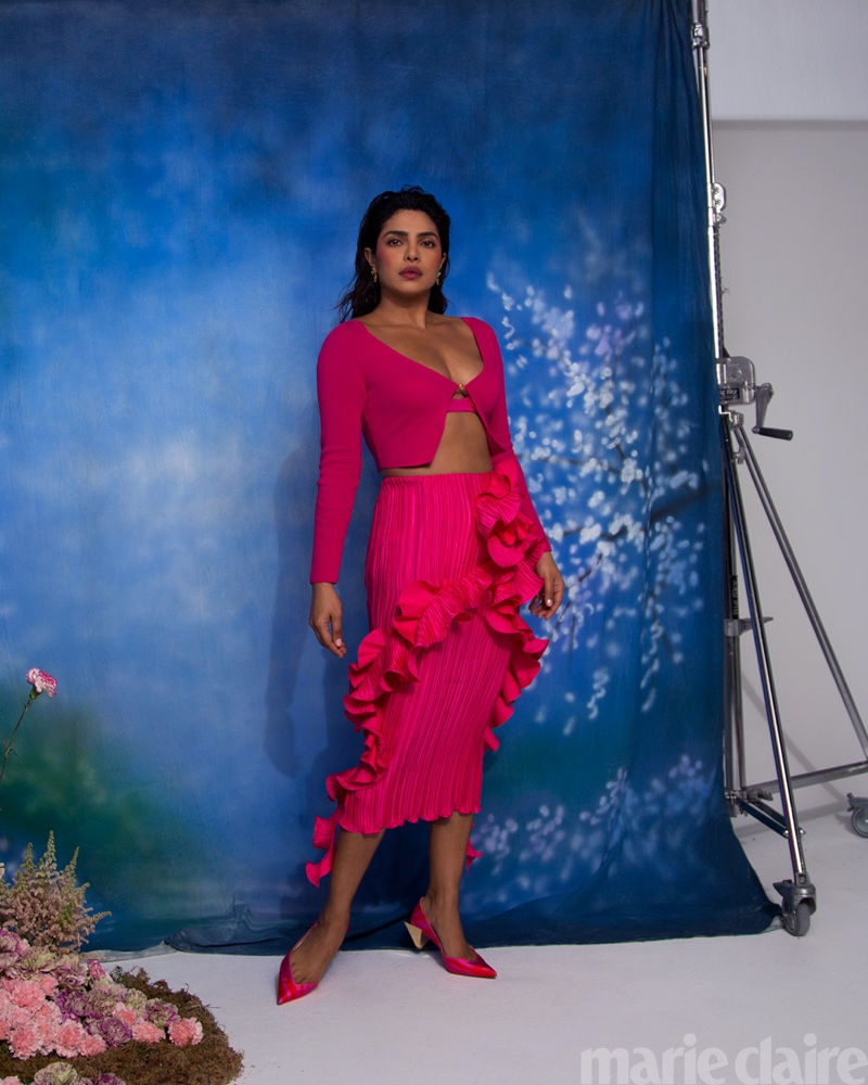 Taking a stand, Priyanka Chopra poses in Versace look, Dolce & Gabbana earrings, and Christian Louboutin shoes.