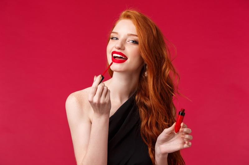 Redhead Woman Applying Red Liquid Lipstick