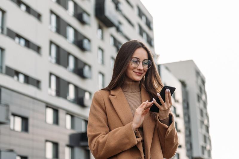 Stylish Woman Brown Coat Glasses Looking Phone