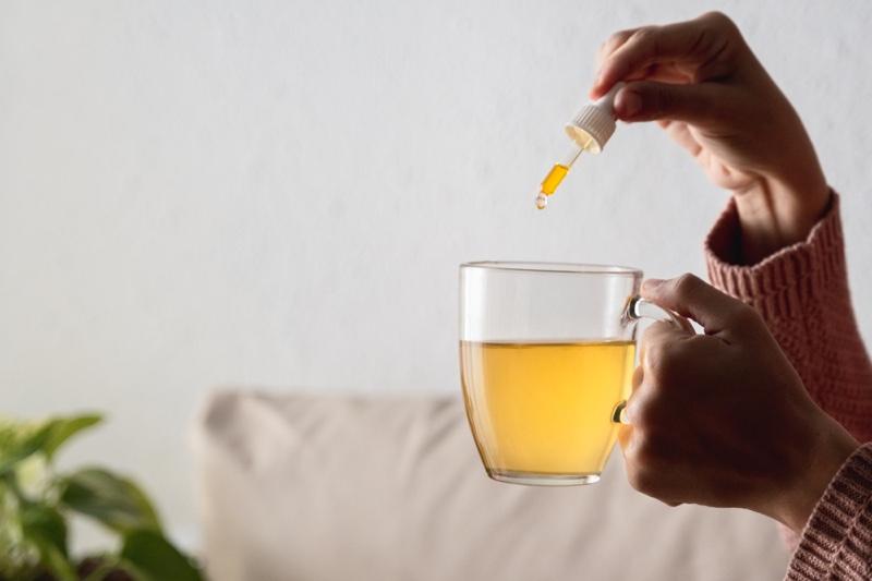 Woman Adding CBD Oil Tea Cup