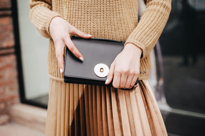 Woman Holding Black Clutch Brown Outfit Cropped