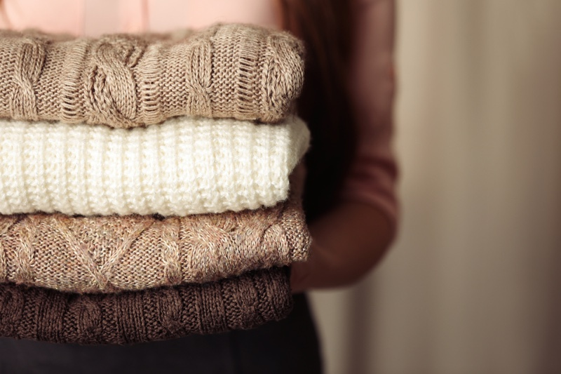 Woman Holding Folded Sweaters Knit Fabric
