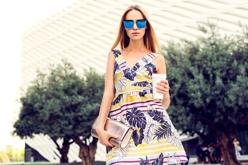 Woman Tropical Print dress Coffee Cup Silver Clutch Blue Sunglasses