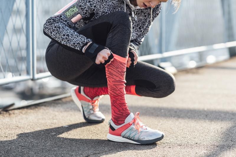 Activewear Female Runner Pulling Pink Socks Sneakers