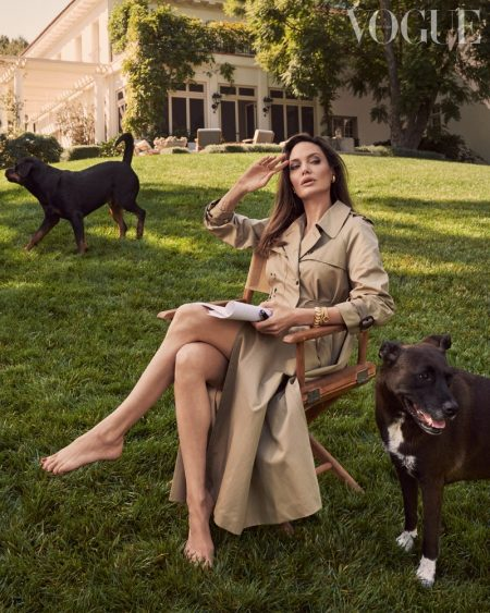 Posing with her dogs Dusty and Sophia, Angelina Jolie wears a Dior trench coat.