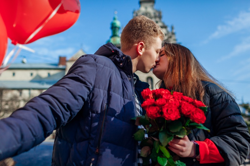 Couple Kissing Woman Holding Bouquet Roses red