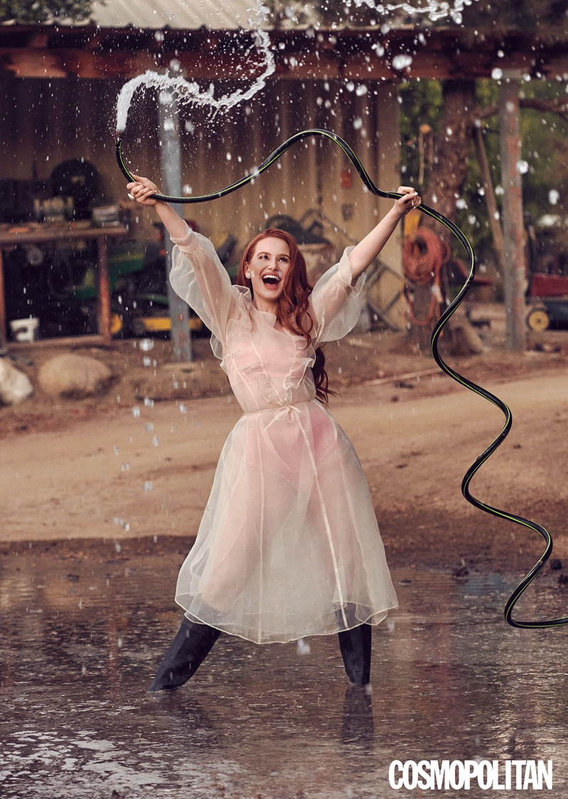 Posing with a hose, Madelaine Petsch wears a pink Sandy Liang dress and bralette with La Chameau boots.