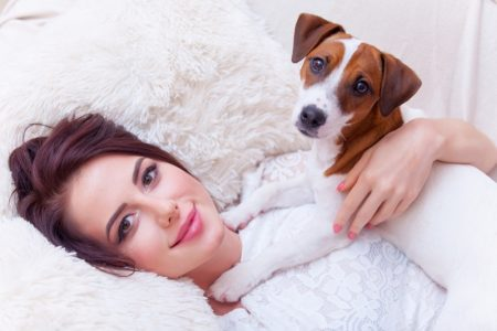 Model Smiling Holding Dog Laying Down