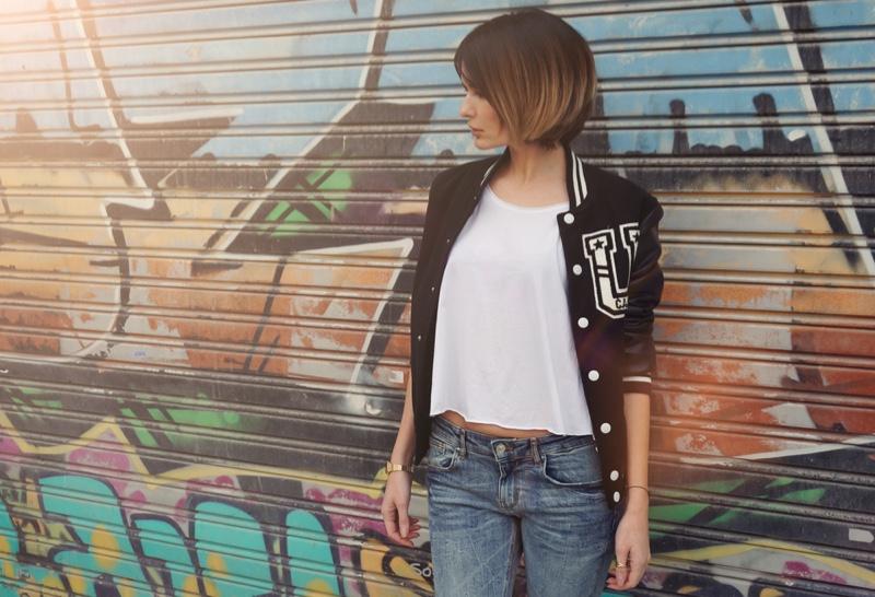 Model Wearing Letterman Jacket White T-Shirt Jeans Graffiti Background