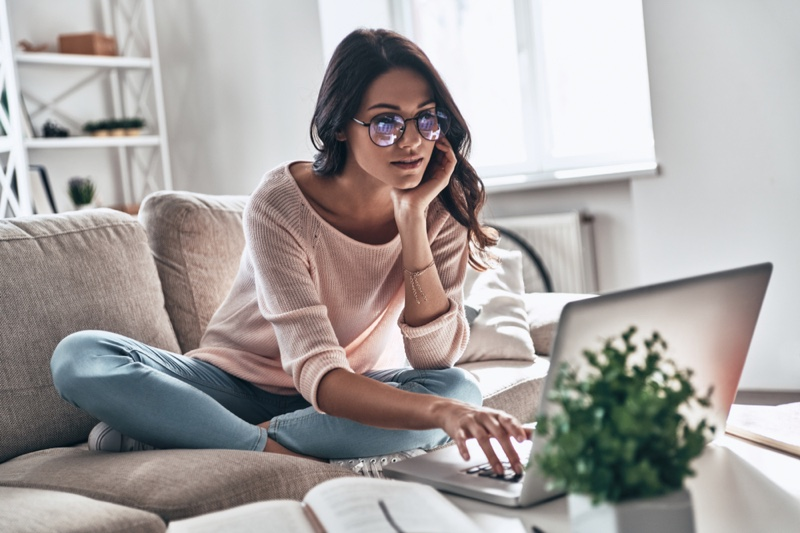 Sitting Couch Woman Viewing Laptop Pink Sweater