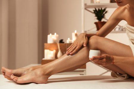 Woman Applying Balm Legs Lotion