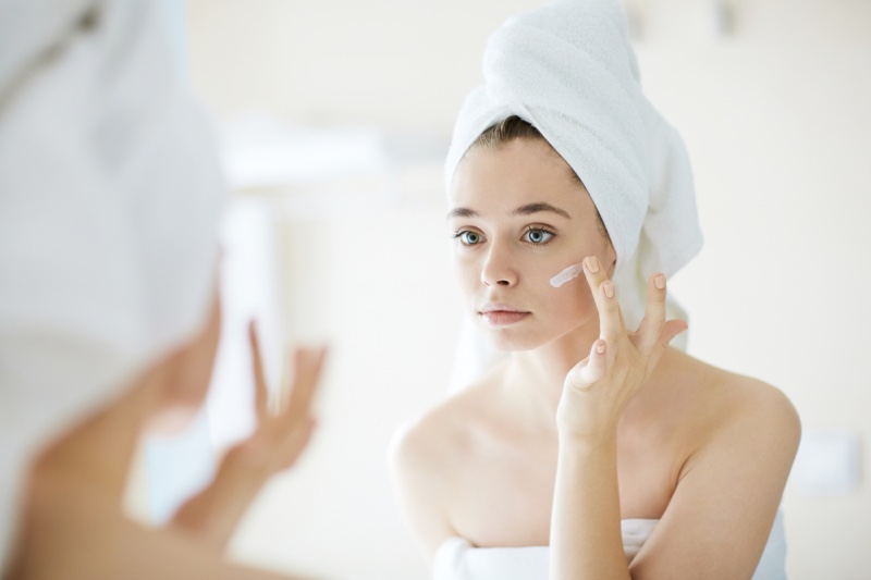Young Woman Applying Cream Face Mirror