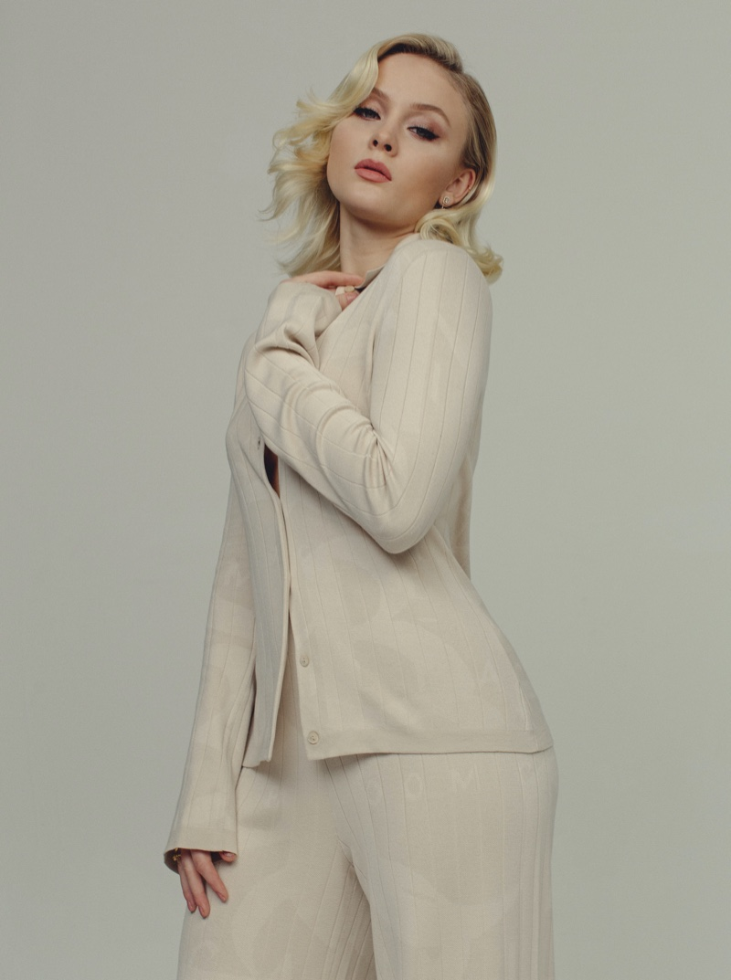 Dressed in white, Zara Larsson poses in knit separates. Photo: Luc Coiffait