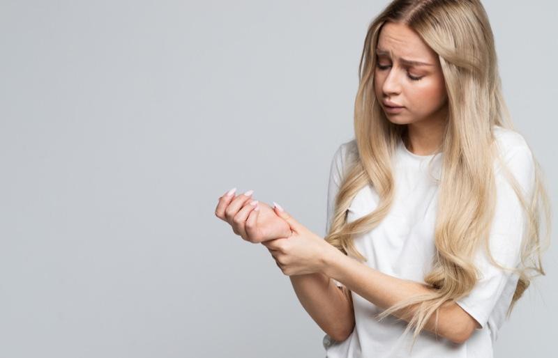 Blonde Woman Long Hair Holding Wrist Injury Chronic Pain